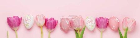 复活节贺卡,上面有复活节彩蛋和郁金香花,背景是粉红色的.带有复制空间的顶视图平面布局