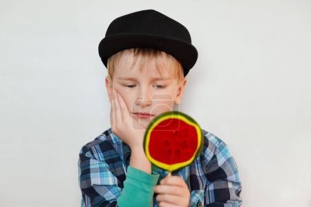 关闭了画像的美丽小男儿童帽,一个手里拿着巨大棒棒糖