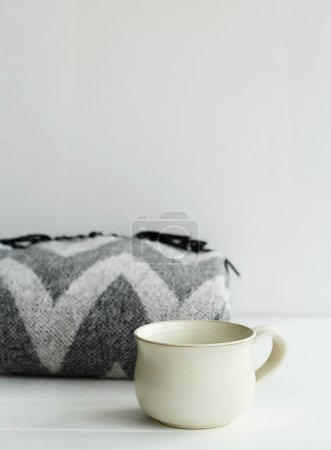 Picture  of warm plaid and cup of coffee or tea over white backg