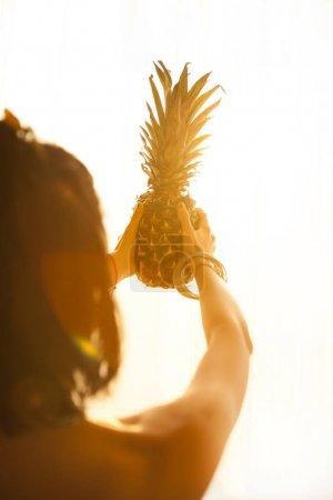 女手控股成熟菠萝白色明亮的背景上