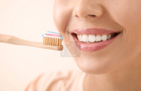 Beautiful young woman with tooth brush on light background, closeup