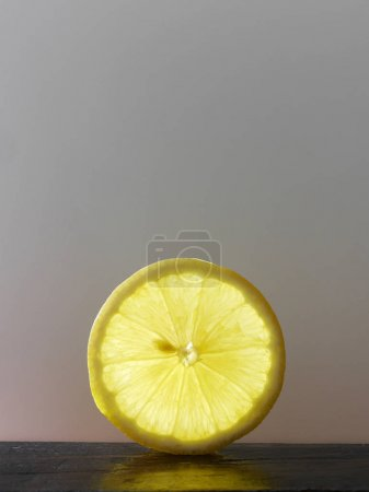 Lemon slice on wooden surface on gray background. Minimalistic food background.