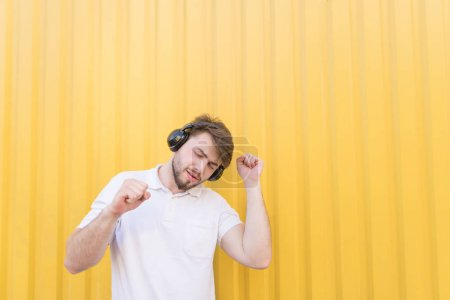 A handsome man listens to music in wireless headphones and dances against the backdrop of a yellow wall. Musical concept