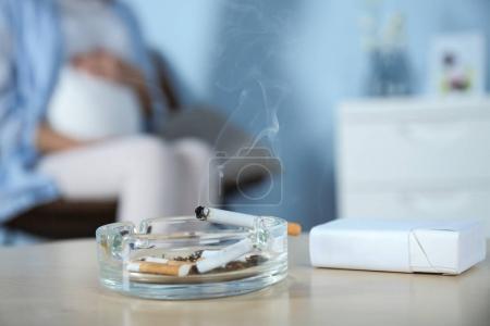 香烟在烟灰缸里和模糊的孕妇背景