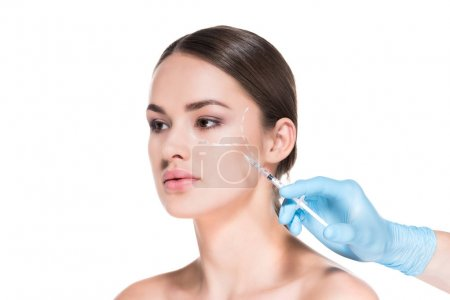 cropped shot of doctor making beauty injection for young woman while she looking away isolated on white
