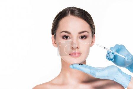 拍摄的医生做美容注射漂亮的妇女在白色隔离