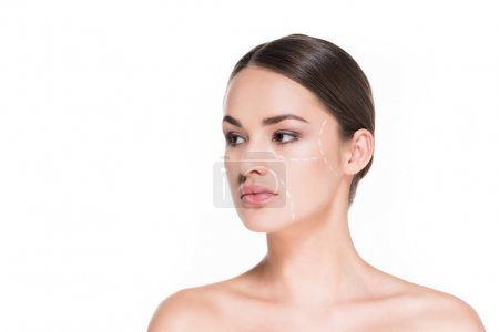 美丽的年轻女子用虚线画在脸上的整形手术在白色隔离