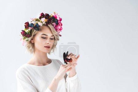 美丽温柔的年轻女子摆在花瓣花圈与蝴蝶在手上, 孤立的灰色