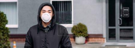 戴口罩的年轻亚洲男子站在街上看着相机的全景照片