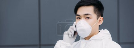 panoramic shot of asian epidemiologist in hazmat suit and respirator mask talking on smartphone and looking at camera