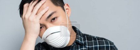 panoramic shot of young asian man in respirator mask touching forehead and looking at camera while suffering from headache isolated on grey