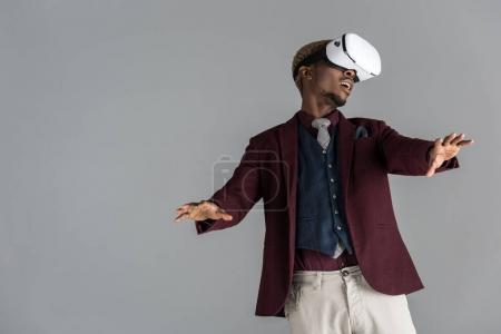 年轻的非洲裔美国人在 vr 耳机与手臂伸展灰色背景