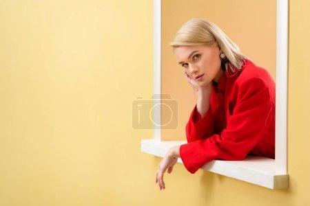 年轻时尚女人的侧面观看红色西装寻找装饰窗口