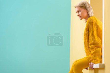 穿黄色毛衣和紧身衣的时尚女人的侧面装饰窗口
