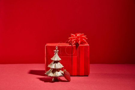 red gift box and decorative golden Christmas tree with bauble on red background