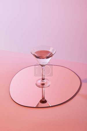 cocktail glass with liquid on mirror with reflection on pink background
