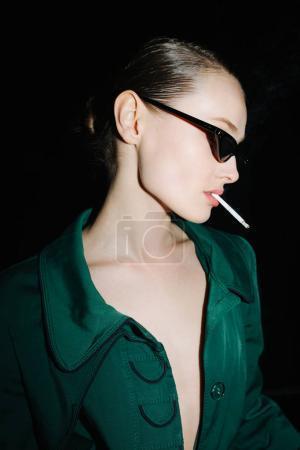 时尚太阳镜的年轻女士的肖像站立和吸烟, 而一边看着黑色背景隔离