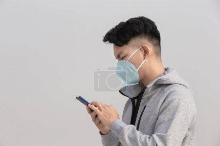 男人用带口罩的智能手机