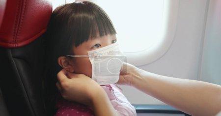 由于飞机上可传染的传染病,亚洲父母给孩子戴上口罩