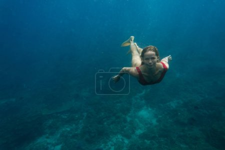 游泳衣中年轻女子的水下照片和在海洋中独自潜水的鳍