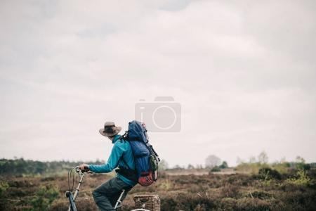 Traveler on bicycle looking over moorland