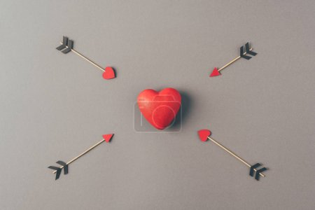 top view of red heart between four arrows on gray, valentines day concept