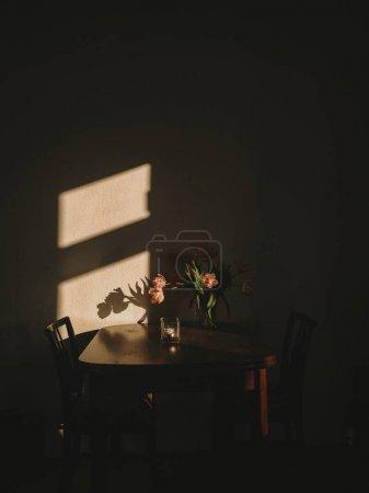 木制老式书桌上美丽的花朵和清晨的阳光照耀着创造的阴影