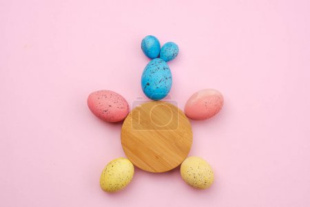 Closeup of a rabbit made of eggs and a wooden circle on the tabl