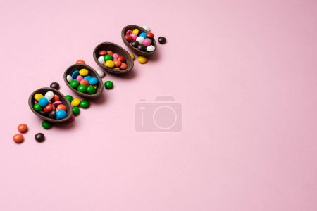 Easter pink background with multi-colored candy in a chocolate n
