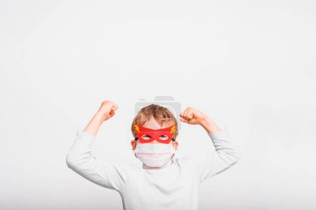 A boy with a fun superhero mask to protect himself from the viral infections of the disease.