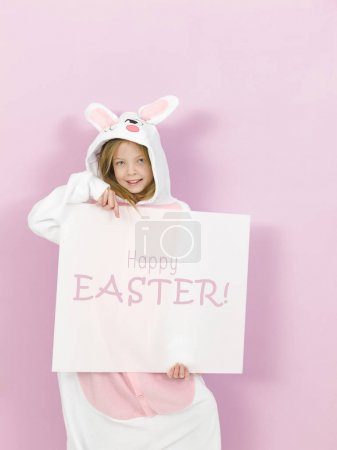 pretty blonde girl in cozy rabbit costume holding white board with text happy easter and posing in studio