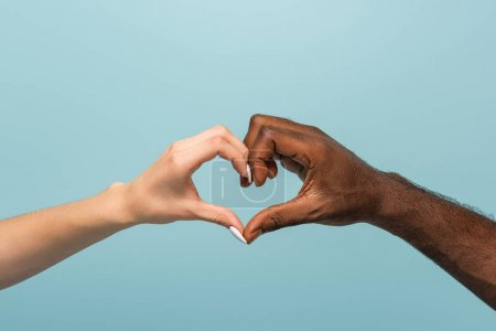 cropped view of interracial couple showing heart gesture isolated on blue