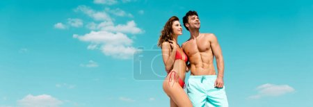 smiling young couple together against blue sky with clouds, panoramic shot