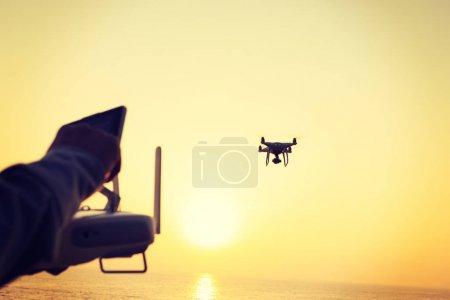 女子手持遥控飞行无人机在日出海面拍照