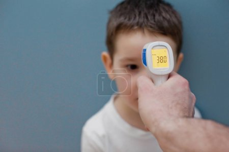 用红外温度计测量蓝色背景下的儿童体温