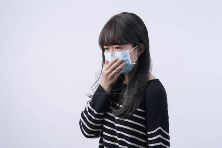 Woman coughing with mask - young Asian covering the mouth, feeling unwell with wearing medical blue face mask isolated on white background, close up.