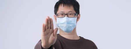 一名年轻的亚洲男子的画像,他说,不要戴医用手术用蓝色面罩感染大头牛,这种面罩在白色背景下被隔离开来,特写特写,特写.