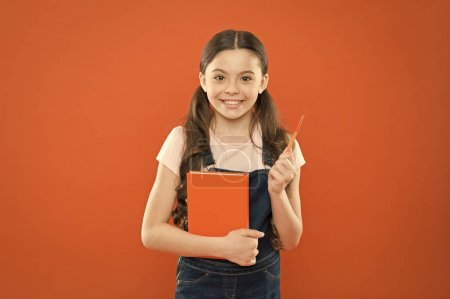 Doing research. literature lesson. back to school. happy little girl with notebook. school girl read book on orange background. writing notes. kid diary. poetry and novel. modern education