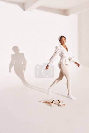 full-length photo of dark-skinned ballerina on white background with shadow on it, she wearing white shirt, beige bodysuit, white tights she stands near her pointes and looks down