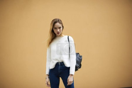 Beautiful female dressed in white sweater standing on copy space for advertising