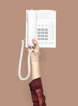 手持旧电话的一人手的部分视图