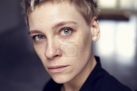 年轻美貌雀斑女人脸肖像与健康的皮肤和短头发,绿色的眼睛