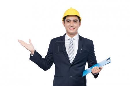 年轻建筑师的男人时,持有剪贴板和姿态的安全帽