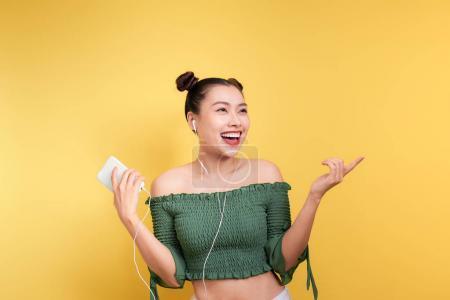 美丽的年轻亚洲妇女在耳机听音乐和唱歌在黄色背景下