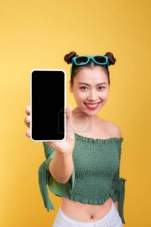 一个开朗可爱的女人的肖像显示空白智能手机屏幕上的黄色背景隔离