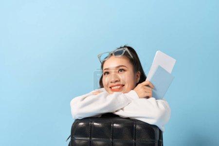 年轻的亚洲妇女坐在一个手提箱附近,在蓝色背景上拿着护照.