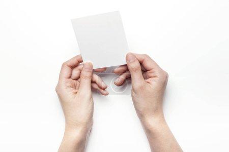 拿着一张白色的明信片.