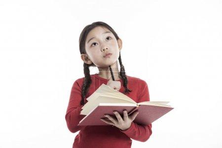 小女孩拿着一本书, 而站在工作室, 孤立的白色背景