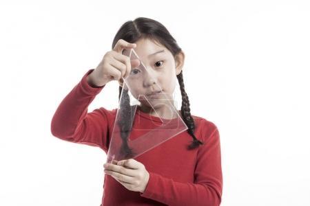 美丽的亚洲小女孩拿着一套正方形.