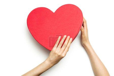 女人的手拿着一个被白色隔离的心盒.